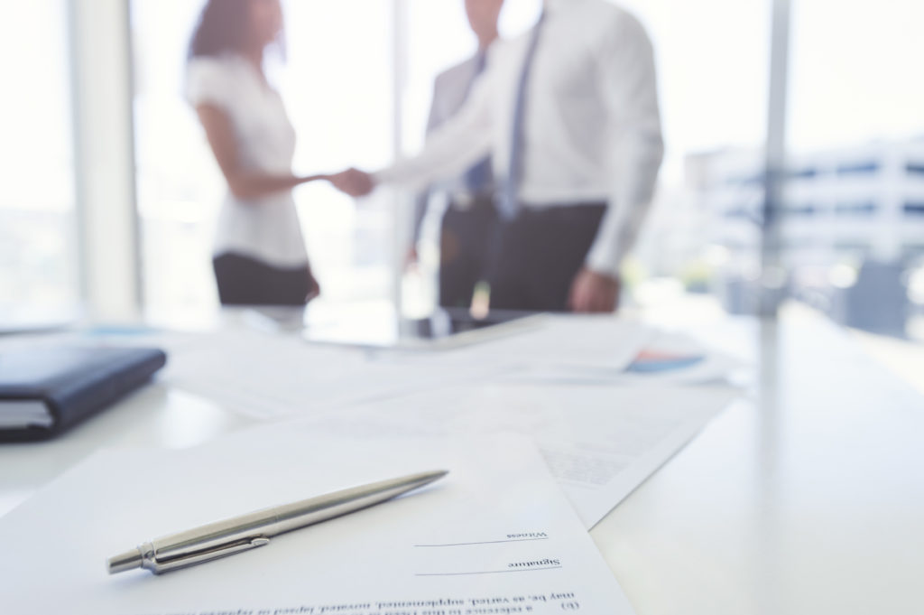 Blurry image of a vendor and company shaking hands after signing a deal